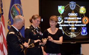 Maj. April M.K. Moore receives the Roman Gladius sword, signifying her selection as the LTC Ronald C. Ward Distinguished Special Operations Forces Student Award for the Command and General Staff Officer Course Class of 2016. Presenting is Col. Paul Schmidt, director of the Combined Arms Center Special Operations Forces Directorate, and Ms. Beth Ward, wife of the late Lt. Col. Ward.