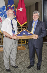Brig. Gen. (Ret.) John Schmader presents Col. (Ret.) Lynn Rolf with his retirement flag during his retirement ceremony Aug. 4. – Click the image for more photos from the ceremony.