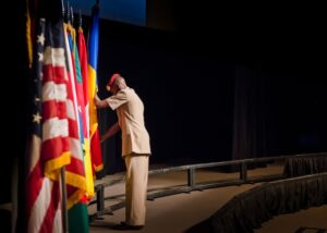 Capt. Amir Nimery posts the flag of Chad during the International Flag Ceremony Aug. 14.