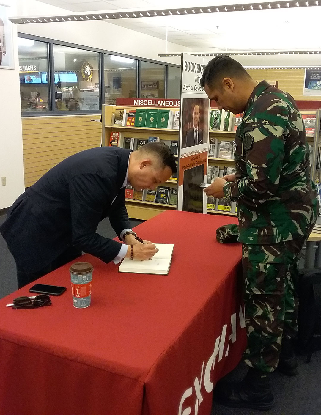 "Lt. Col. David Oakley, an assistant professor at the National Defense University and author of ""Subordinating Intelligence: The CIA/DoD Post-Cold War Relationship,"" signs his book for a CGSC student in the AAFES Bookstore in the Lewis and Clark Center on April 17."