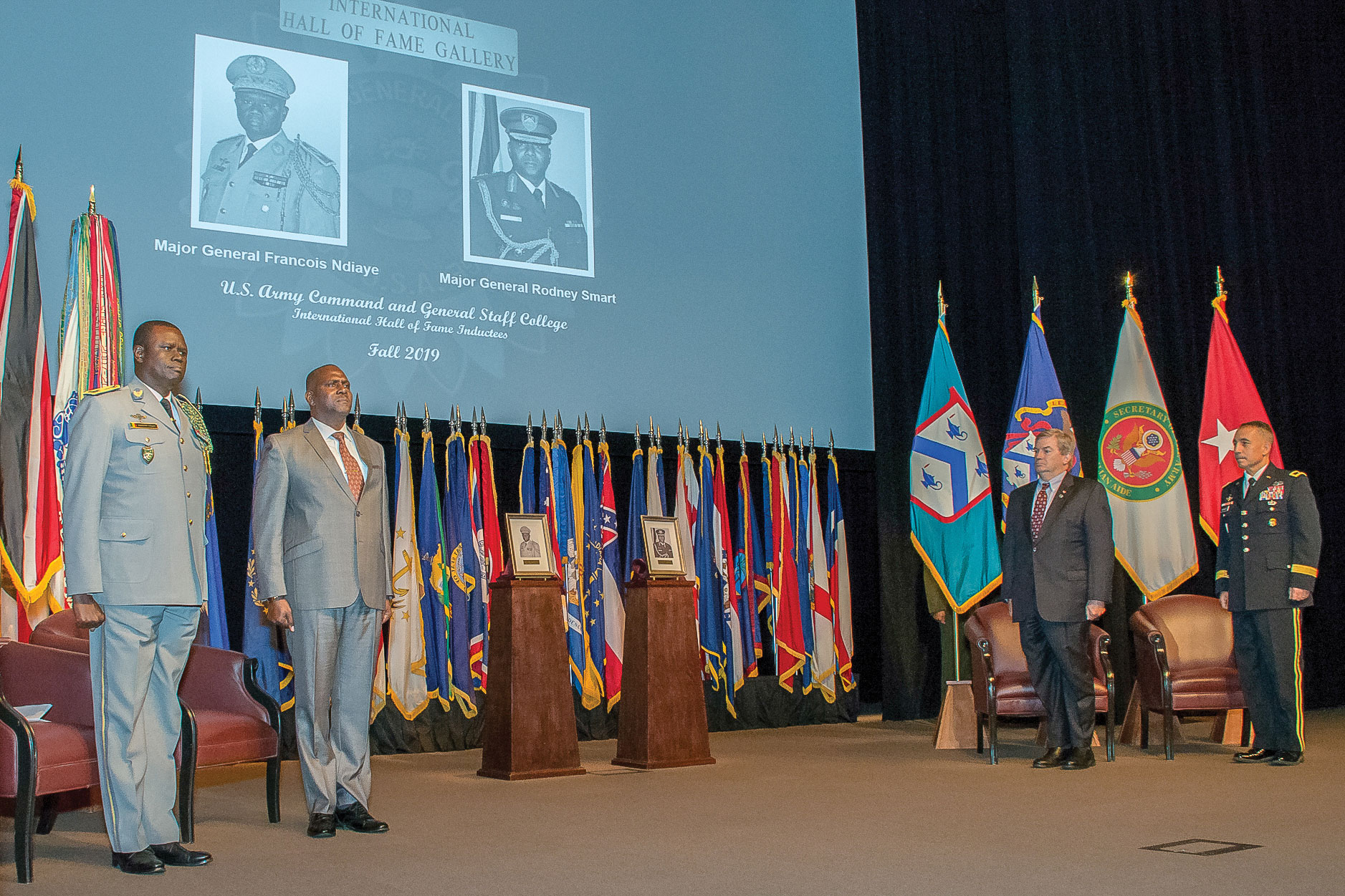 Photo of IHOF inductees Maj. Gen. Francois Ndiaye, chief of staff of the Senegalese Army, CGSC class of 1994; and retired Maj. Gen. Rodney Smart, former chief of Defence Staff of the Trinidad and Tobago Defence Force, CGSC class of 2009-01, along with CGSC Foundation Chairman Mike Hockley and CGSC Deputy Commandant Brig. Gen. Stephen Maranian stand at attention as the national anthems of each country are played at the end of the ceremony Oct. 3, 2019, at the Lewis and Clark Center.