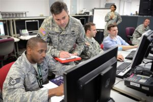 """Air Force Staff Sgt. Presky, left, Army Master Sgt. McCarthy and civilian personnel concentrate on exercise scenarios during """"Cyber Guard 2015"""" in Suffolk, Va., June 11, 2015. Partners from across government, academia, international coalition and industry attended the two-week exercise, where participants performed operational and interagency coordination as well as tactical level operations to protect, prevent, mitigate and recover from a cyberspace incident. (DoD photo by Marvin Lynchard)"""