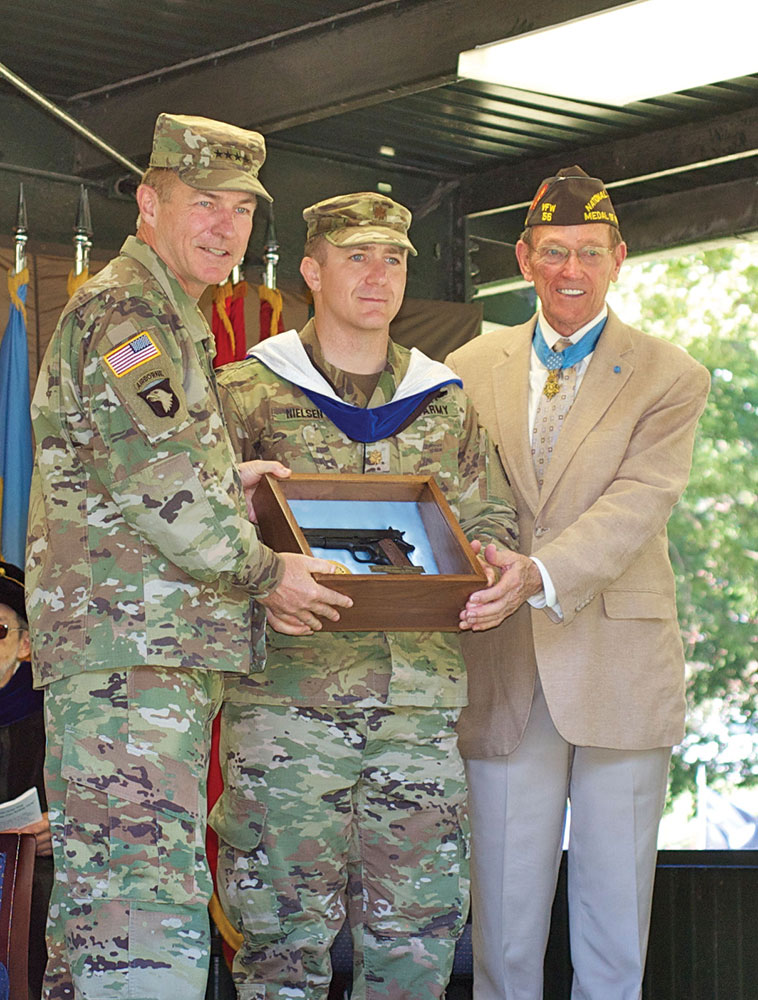 Major Jonathan Nielsen receives the General George C. Marshall Award as the top U.S. graduate from Army Vice Chief General James C. McConville, left, and Col. (Ret.) Roger Donlon, Medal of Honor Recipient, who is also a former member of the CGSC faculty and a founding trustee of the CGSC Foundation.